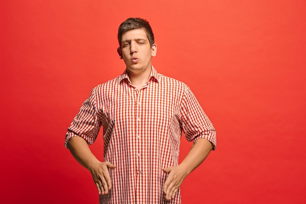 Argue, arguing concept. funny male half-length portrait isolated on red. young emotional surprised man