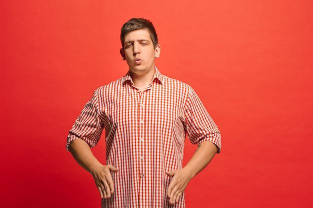 Argomenta, argomentando il concetto. ritratto a mezzo busto maschio divertente isolato su colore rosso. giovane uomo sorpreso emotivo