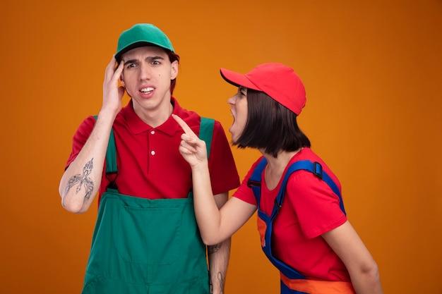 Litigare giovane coppia in operaio edile uniforme e berretto ha sottolineato il ragazzo che tocca la testa guardando giù ragazza arrabbiata in piedi in vista di profilo guardando e gridando al ragazzo che alza il dito