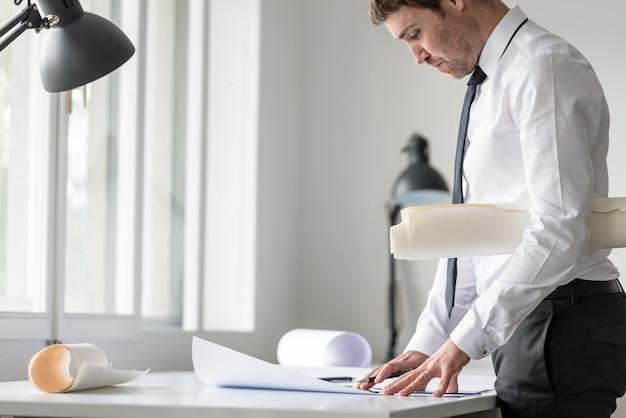 ビジネスマンまたは計画で作業中に定規と鉛筆を使用して白いシャツのarhitect