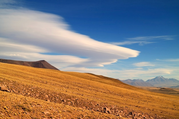 The arid foothill of los flamencos national reserve with the amazing lenticular clouds chile
