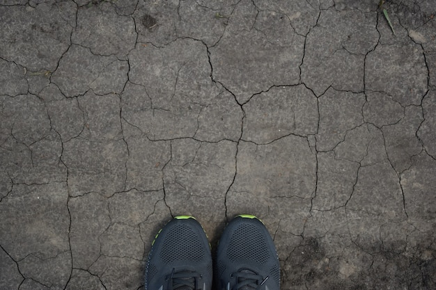 On arid ground, cracked everywhere at the bottom of the frame, two sneakers peek out. there is plenty of space at the top to insert a lettering