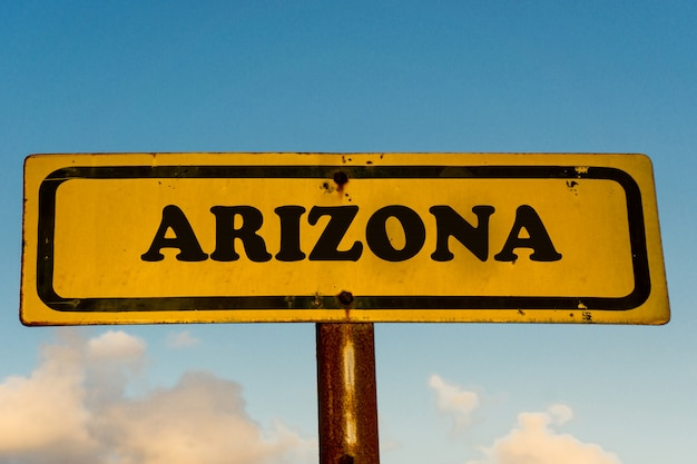 Arizona state on old yellow sign with blue sky