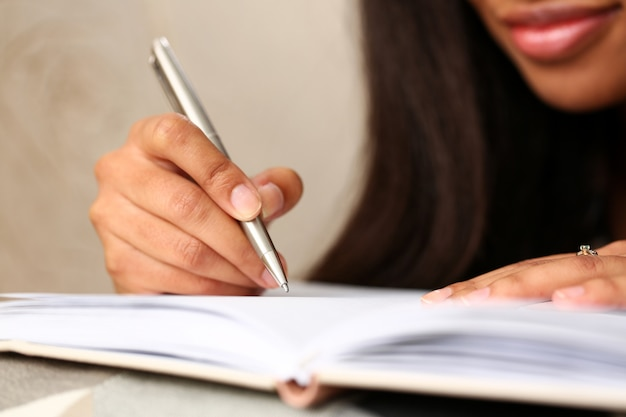 Arm of black woman write story in notebook