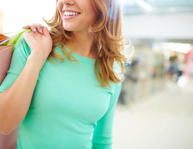Braccio primo piano della donna con le borse della spesa