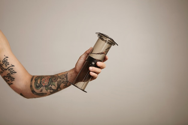 Arm and hand holding an aeropress with some clean water on light gray