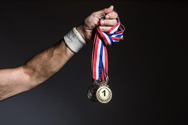 어두운 배경에 3개의 금, 은, 동메달을 들고 있는 노인 운동선수의 팔. 스포츠와 승리 개념입니다.