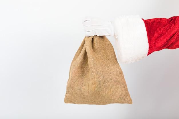 Рука санта-клауса мешок на белом фоне