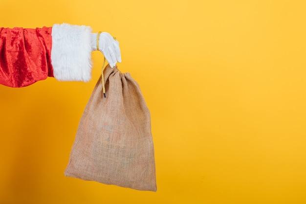 Рука санта-клауса мешок на желтом