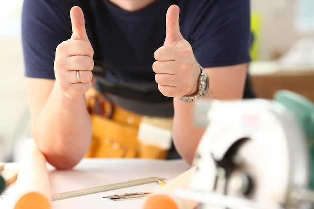 労働者の腕のショーは親指を上にしてサインを確認します