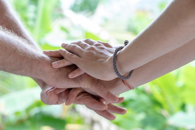 Руки сложены одна за другой в единстве и совместной работе. многие руки собираются вместе в центре круга. закройте открытый выстрел. многие руки соединяются в природе.