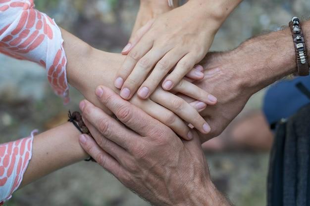 団結とチームワークで腕を一つずつ積み重ねました。多くの手が円の中心に集まっています。
