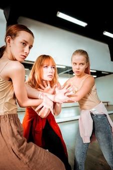 腕のストレッチ。赤い髪の美しいダンスの先生と彼女の生徒たちは腕のストレッチをしながら集中しているように見えます