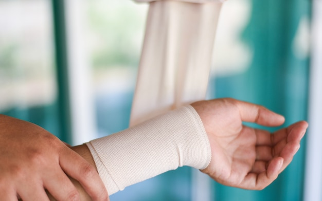 Arm wound bandaging hand and by nurse