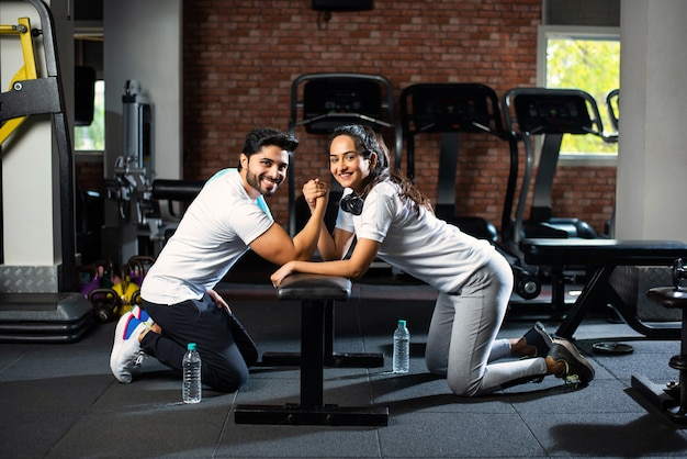 젊은 인도 아시아 부부 사이의 팔 레슬링 도전-체육관에서 재미