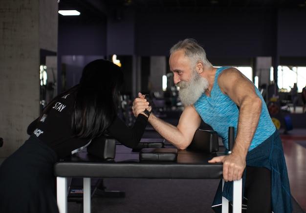 Arm wrestling challenge between a senior couple.