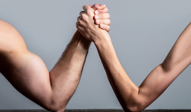 Arm wrestling. heavily muscled man arm wrestling a puny weak man. arm wrestling thin hand and a big strong arm in studio. two man's hands clasped arm wrestling, strong and weak, unequal match.