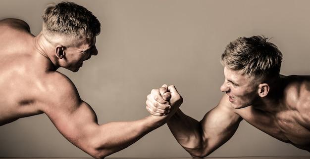 Арм-рестлинг. двое мужчин по армрестлингу. мужчины меряют силы, оружие. ручная борьба, соревнования. соперничество, крупный план мужского армрестлинга. руки или руки человека. мускулистая рука.