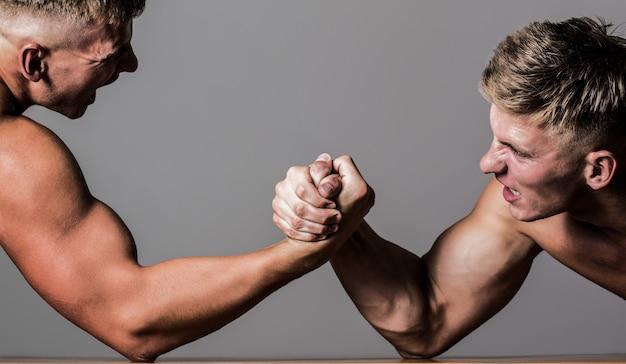 Арм-рестлинг. двое мужчин по армрестлингу. соперничество, крупный план мужского армрестлинга. две руки. мужчины меряют силы, оружие. ручная борьба, соревнования. руки или руки человека.