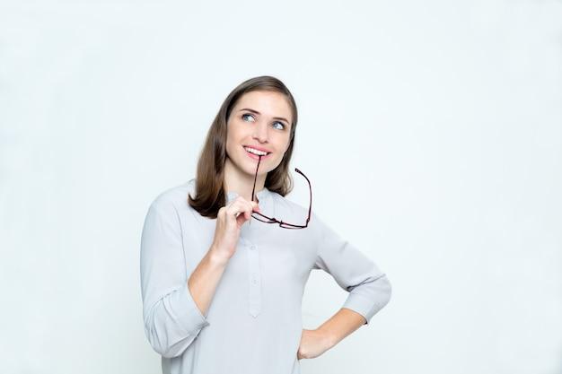 Крупным планом улыбается мечтательной женщина кусает очки arm