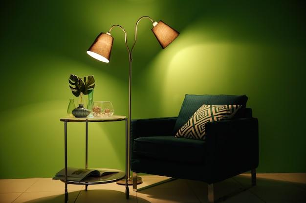 緑の壁の表面に家の装飾が施されたアームチェア、ランプ、テーブル