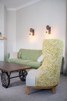 アームチェア、リビングルーム。リビングルームの低いテーブルとソファの近くに高い背もたれ模様の表面を備えた布張りのデザイナーアームチェア