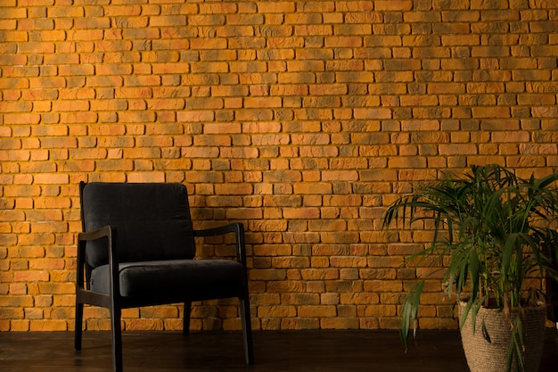Armchair near the yellow brick wall and palm tree in a pot