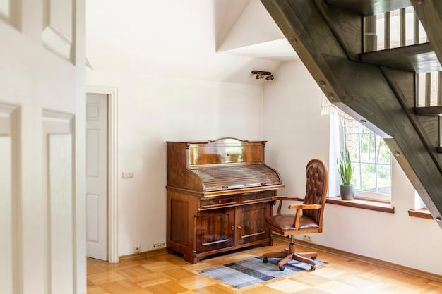 식물과 계단이 있는 흰색 거실 내부의 나무 피아노 옆 양탄자에 있는 안락의자. 실제 사진