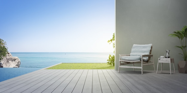 Кресло на террасе возле бассейна и сада в современном пляжном домике