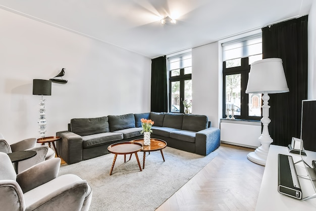 Кресла и диван, расставленные вокруг стола с цветами в светлой гостиной современного дома