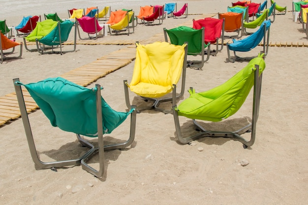 Armchairs with soft pillows on the sandy shore