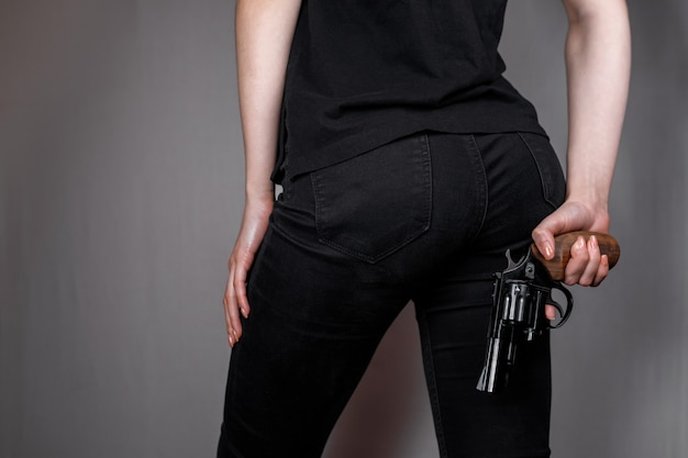 Armed girl in black jeans hides her pistols gun behind her back. hidden threat killer woman.