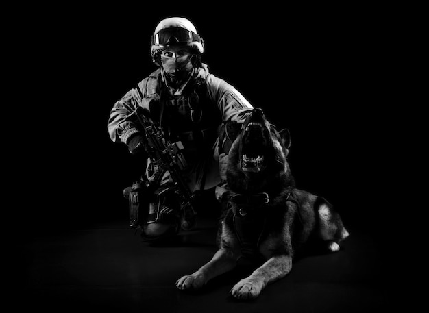 軍服を着た武装した男が捜索犬の隣に座っています。ミクストメディア