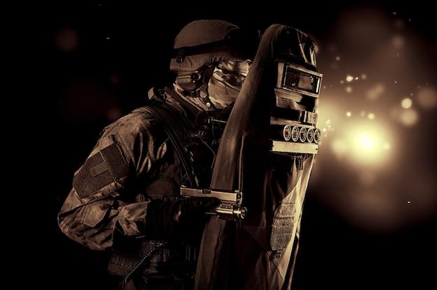 ピストルで武装した防弾チョッキを着た軍人が盾で身を覆っている。ミクストメディア