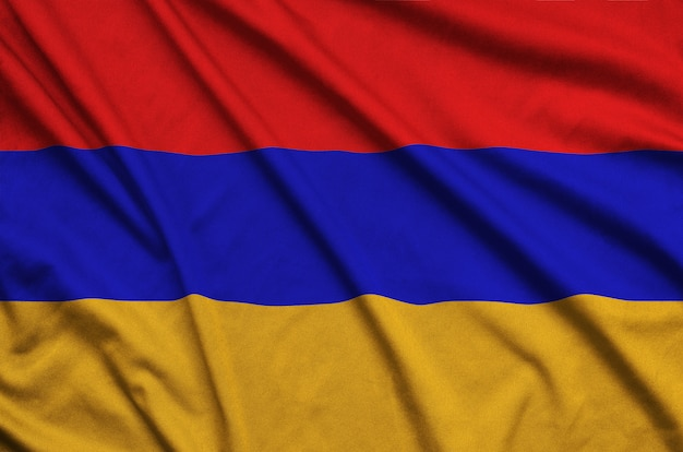 Armenia flag is depicted on a sports cloth fabric with many folds.