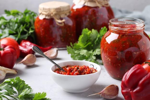 Армянская аджика из красного перца, помидоров, чеснока, кинзы и петрушки в миске и банках, а также свежие ингредиенты на столе. натюрморт на серой поверхности.