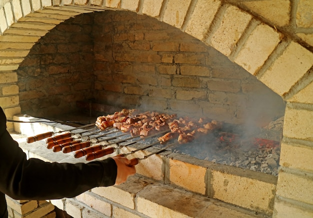 Armenian barbecue or khorovats being grilled on a traditional clay oven