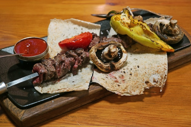 Armenian traditional barbecue or khorovats with grilled vegetables on flatbread called lavash
