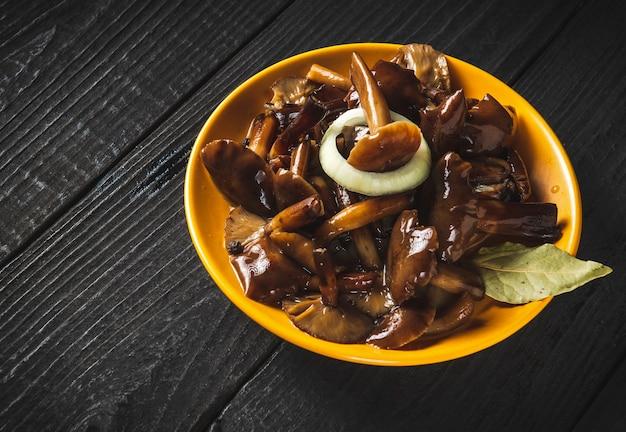 Armillaria mellea 또는 꿀 균류를 빈티지 테이블에 향신료와 양파와 함께 노란색 접시에 절인.