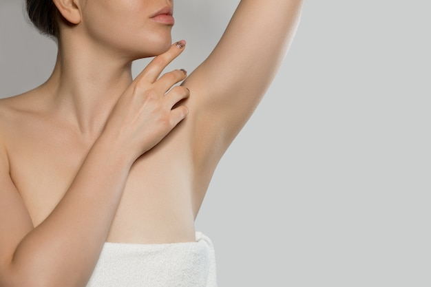 Armpit epilation, lacer hair removal. young woman holding her arms up and showing clean underarms, depilati on smooth clear skin .beauty portrait. skin care.