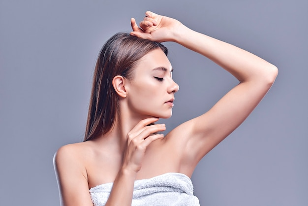 Armpit epilation, lacer hair removal. young woman holding her arms up and showing clean underarms, epilation on smooth clear skin .beauty portrait. skin care.