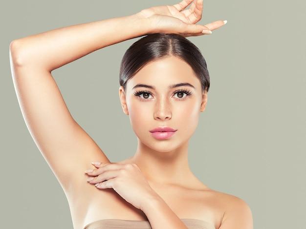 Женщина концепции депиляции кожи подмышки здоровая рука вверх. цветной фон. студийный снимок.