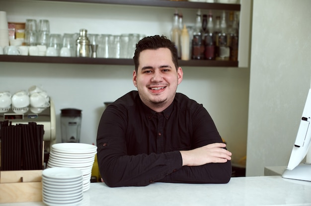 An arms crossed handsome man smiling behind the bar