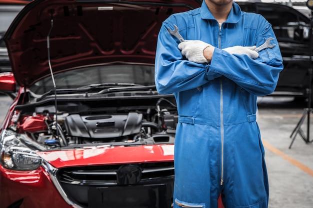 自動車整備士が車のサービスとメンテナンスを行う腕を組んだ。