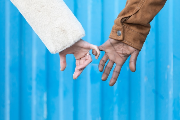 Arms of interracial couple holding hands, great love symbolic concept,