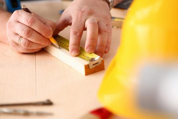 木製のバーのクローズアップを測定する労働者の腕