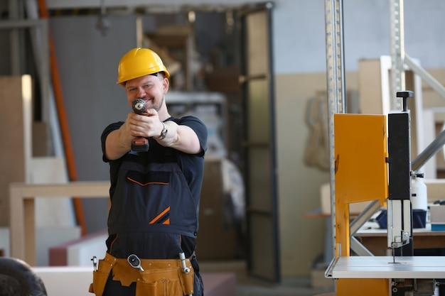 電気ドリルのクローズアップを使用して労働者の腕