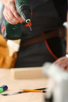 電気ドリルを使用して労働者の腕