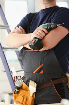 電気ドリルを使用する労働者の腕