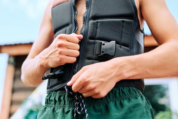 야외 스포츠 대회에 참가하려고 하는 동안 검은색 안전 재킷을 입고 지퍼를 잠그는 젊은 활동적인 스포츠맨의 팔